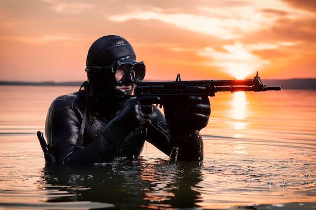 Il marine esce dall'acqua e si avvicina al bersaglio con le armi in mano. il concetto di videogiochi, pubblicità, instabilità nel mondo, conflitti tra paesi. tecnica mista Foto Premium