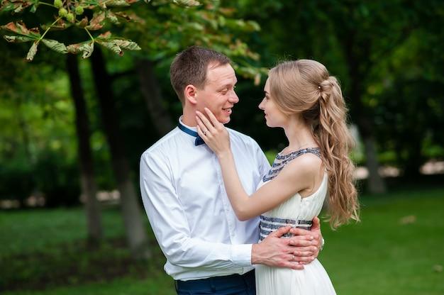 La coppia sposata sta camminando e abbracciando nel parco. Foto Premium