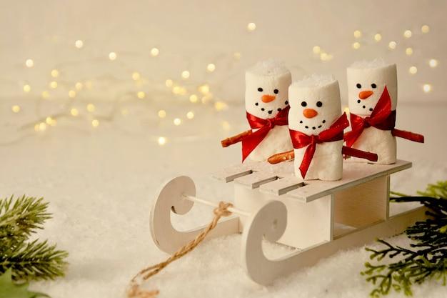Marshmallow pupazzi di neve con slitta, mockup astratto di natale con bokeh e rami di abete Foto Premium