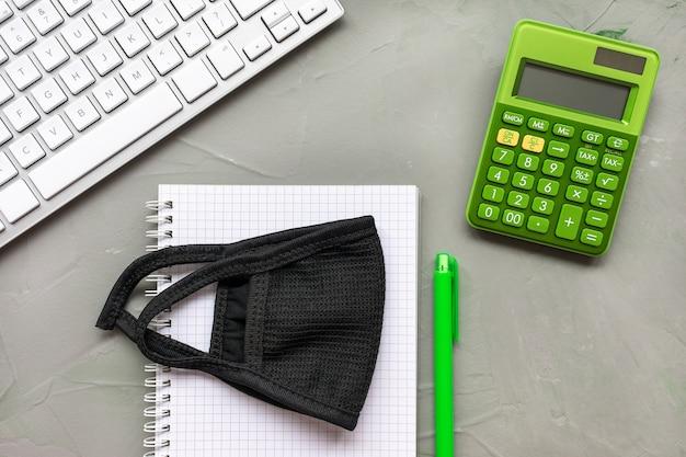 Maschera, tastiera, calcolatrice e taccuino su grigio, piatto laici Foto Premium