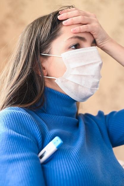 Giovane donna mascherata con mal di testa Foto Premium