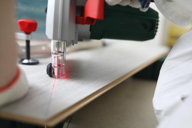 Master taglia il laminato con macchina da taglio laser. Foto Premium