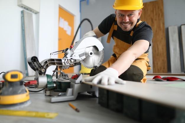 Il maestro con il casco giallo sorride e taglia il pannello laminato con la macchina. Foto Premium