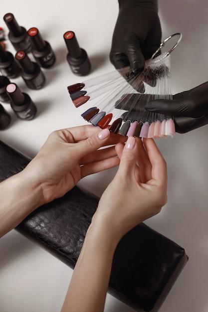Maestro di manicure in guanti neri, ripresa con la tavolozza del cliente, preparazione per l'applicazione del gel polish. strutture termali. sala manicure. Foto Premium