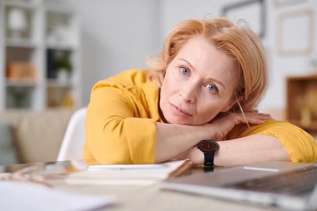 Donna di affari isolata auto bionda matura che ti guarda mentre giaceva sulla scrivania davanti al computer portatile durante il lavoro a distanza a casa Foto Premium