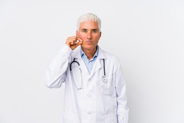 Uomo caucasico maturo di medico con le dita sulle labbra che tengono un segreto. Foto Premium