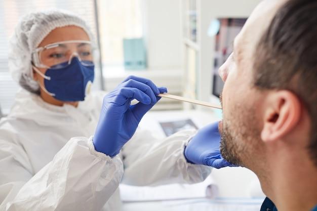 Uomo maturo che apre la bocca mentre medico in abbigliamento protettivo esaminando la sua gola durante l'esame medico all'ospedale Foto Premium