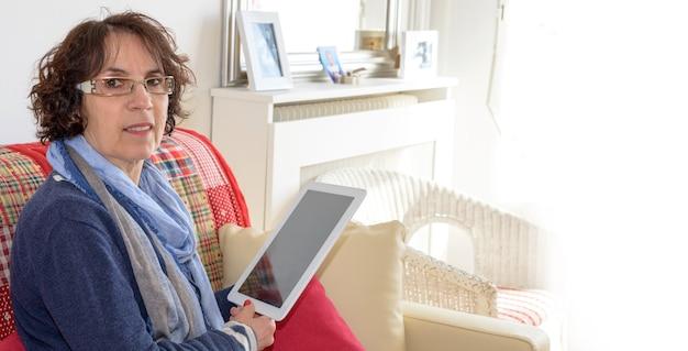 Coppia sorridente con una tavoletta digitale su un divano Foto Premium