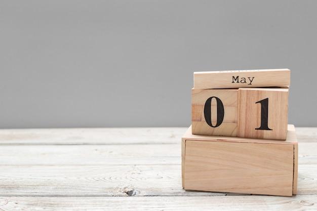 1 ° maggio. immagine del 1 ° maggio calendario di legno di colore sul tavolo di legno. giorno di primavera, spazio vuoto per il testo. giornata internazionale dei lavoratori Foto Premium