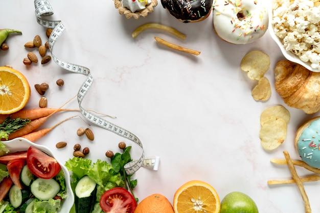 Nastro di misurazione con il concetto di cibo grasso e in forma su sfondo bianco Foto Premium