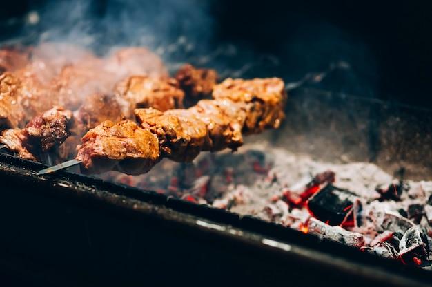 Carne allo spiedo. griglia di maiale. fumare il barbecue in strada. cucinare shashlik di pollo. carboni ardenti. Foto Premium