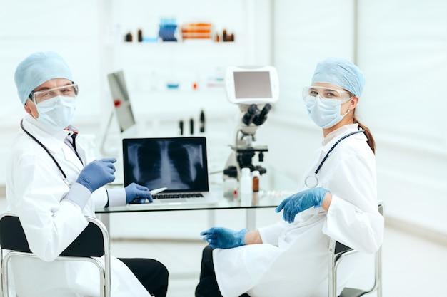 Colleghi medici seduti a un tavolo in laboratorio Foto Premium