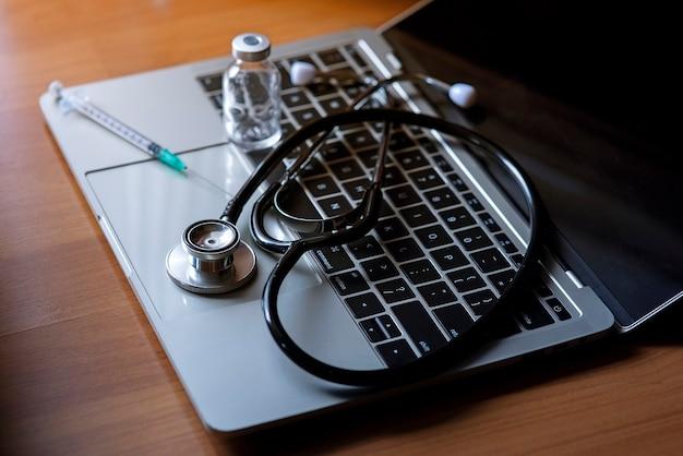 Strumento per esami medici posizionato su un computer notebook Foto Premium