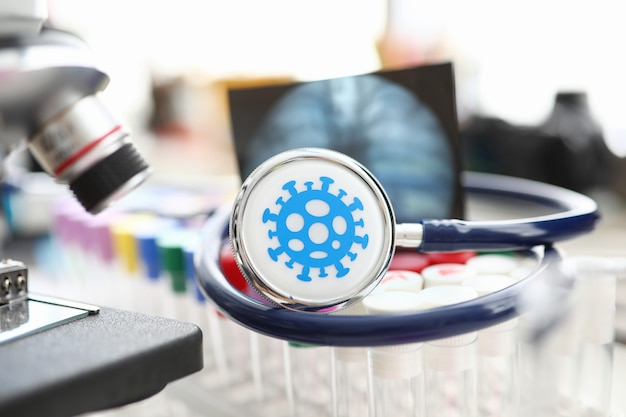Stetoscopio medico che si trova sull'insieme delle fiale al primo piano del laboratorio scientifico. sviluppo del vaccino e concetto di problema del medicinale Foto Premium