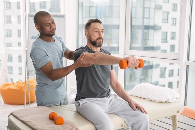 Terapista medico. piacevole simpatico dottore in piedi dietro il suo paziente mentre lo aiuta ad alzare una mano con un manubrio Foto Premium
