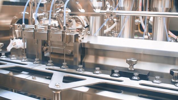 Fiale mediche su una linea di produzione automatica per il riempimento di vaccini e iniezioni. coronavirus Foto Premium