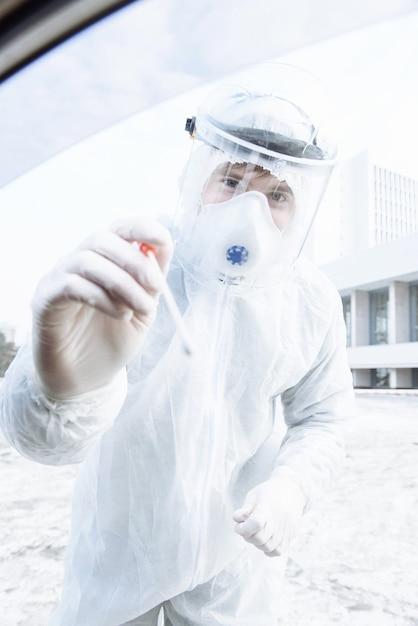 Un operatore sanitario in una tuta protettiva ppe hazmat esegue i test per il virus del coronavirus covid-19 dai conducenti nella loro auto Foto Premium