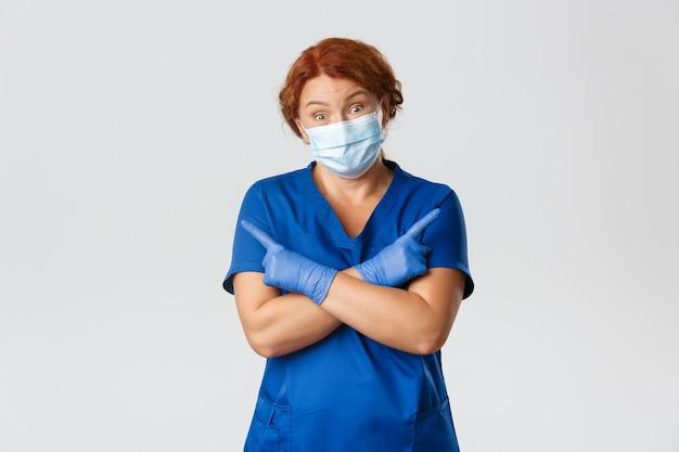 Operatori sanitari, pandemia covid-19, concetto di coronavirus. la dottoressa rossa all'oscuro, l'infermiera in maschera e guanti di gomma non lo sanno, indicando di lato e scrollando le spalle confuso, sfondo grigio. Foto Premium