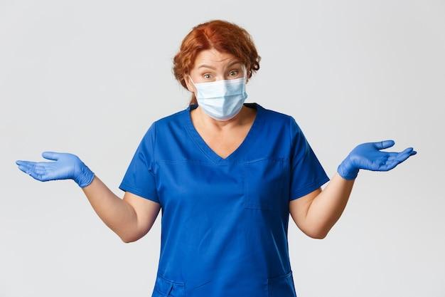 Operatori sanitari, pandemia covid-19, concetto di coronavirus. dottoressa di mezza età rossa confusa e incapace, infermiera ignara, scrolla le spalle e allarga le mani di lato, indossa una maschera, guanti. Foto Premium
