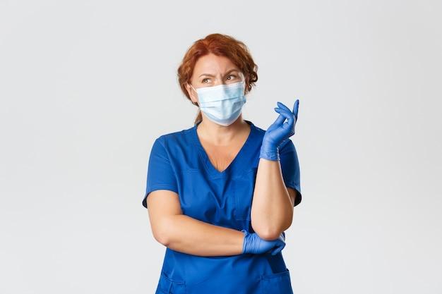 Operatori sanitari, pandemia covid-19, concetto di coronavirus. dottoressa rossa donna confusa e premurosa, infermiera in camice, maschera per il viso e guanti che pensa, sembra indecisa, fa scelte o decisioni Foto Premium