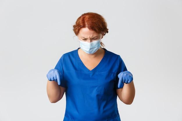 Operatori sanitari, pandemia covid-19, concetto di coronavirus. frustrata dottoressa di mezza età accigliata, infermiera in maschera e guanti accigliata confusa e punta le dita verso il basso, sfondo grigio. Foto Premium