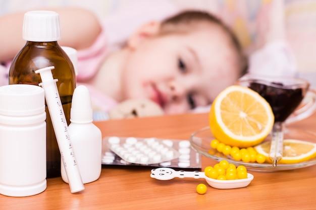 Farmaci e vitamine sul tavolo bambino in un letto che ha la varicella Foto Premium