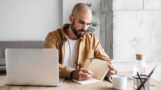 Uomo impegnato del colpo medio che scrive sul taccuino Foto Premium