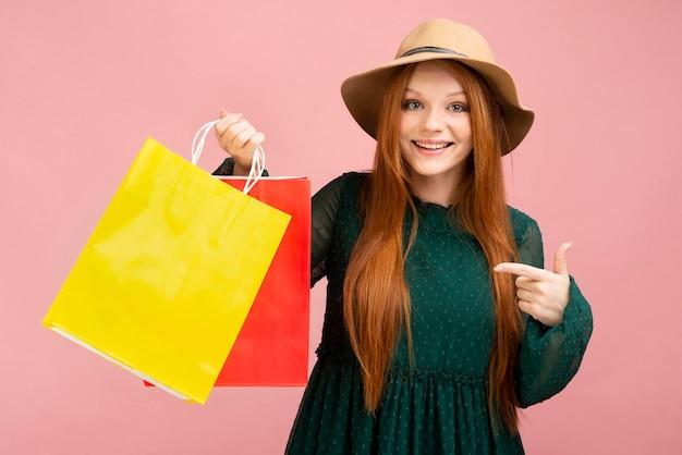 Sacchetti della spesa della tenuta della ragazza del colpo medio Foto Premium