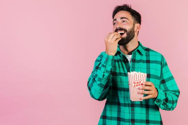 Mezzo colpo felice ragazzo mangiando popcorn Foto Premium