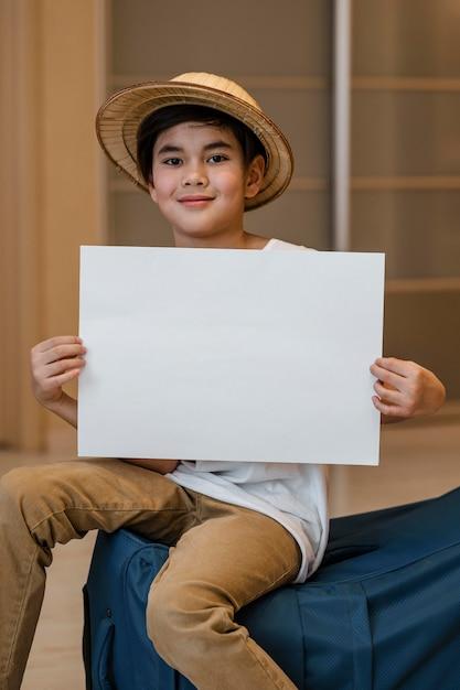 Ragazzo a tiro medio che tiene un pezzo di carta Foto Premium
