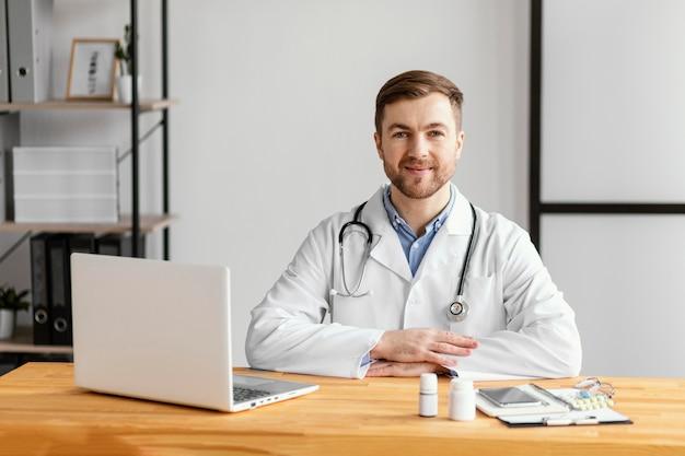 Medico di smiley del colpo medio alla scrivania Foto Premium