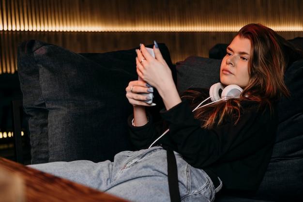 Donna del colpo medio che esamina telefono Foto Premium