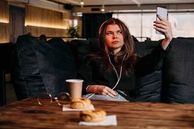 Donna del colpo medio che cattura selfie Foto Premium