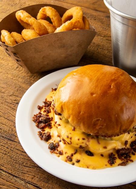 Hamburger fuso del bacon e del formaggio con gli anelli di cipolla sopra fondo di legno Foto Premium