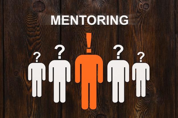 Concetto di mentoring. uomini di carta su legno. Foto Premium