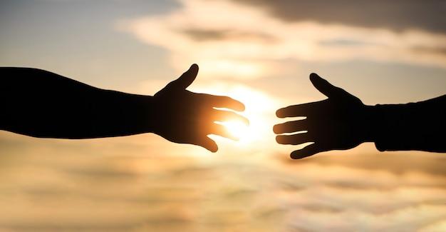 Misericordia, due mani silhouette sullo sfondo del cielo, connessione o concetto di aiuto. Foto Premium