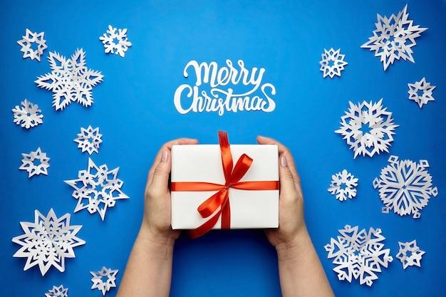 Cartolina d'auguri di buon natale con scatola regalo e fiocchi di neve di carta sull'azzurro Foto Premium