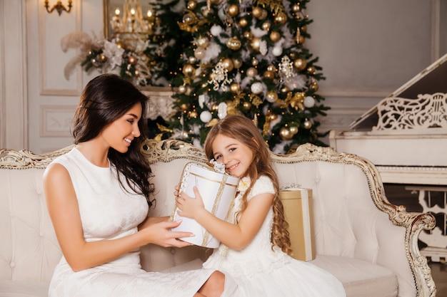 Buon natale e buone feste. la mamma allegra e la sua ragazza carina della figlia si scambiano i regali in piano interno classico bianco e un albero di natale decorato. nuovo anno Foto Premium