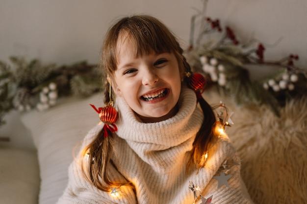 Buon natale e buone feste. ritratto di una ragazza a casa. aspettando natale. Foto Premium