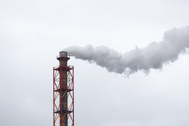 Tubo metallico da cui esce fumo bianco sul cielo nuvoloso Foto Premium