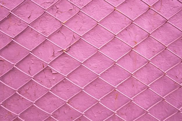 Griglia del filo di metallo sui precedenti di vecchia parete rosa con la pittura della sbucciatura. la trama a maglie come concetto di limitazione della libertà maschile, dipendenza dalle donne, mancanza di libertà, dipendenza Foto Premium
