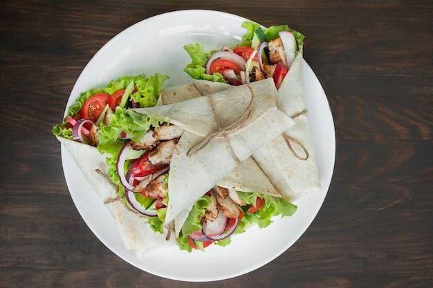 Piatto messicano burrito avvolto con pollo e verdure close-up su un di legno Foto Premium