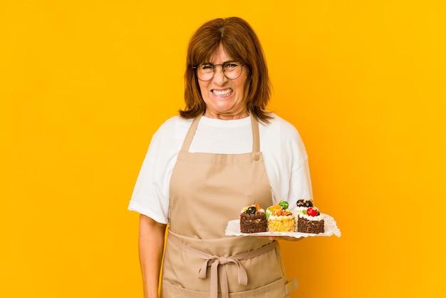 Donna caucasica del cuoco di mezza età che grida molto arrabbiata e aggressiva. Foto Premium