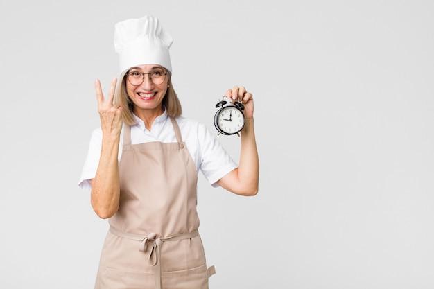 Donna graziosa del panettiere di medio evo che tiene una sveglia Foto Premium