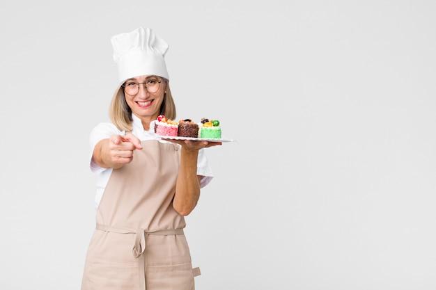 Donna graziosa del panettiere di mezza età con le torte contro la parete dello spazio della copia Foto Premium