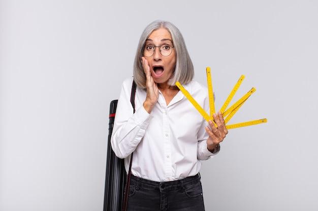 Donna di mezza età che si sente scioccata e spaventata, sembra terrorizzata con la bocca aperta e le mani sulle guance. Foto Premium