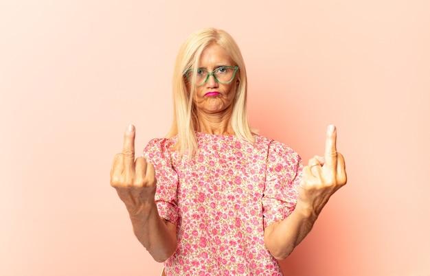 Donna di mezza età che si sente stressata e frustrata, alza le mani alla testa, si sente stanca, infelice e con emicrania Foto Premium