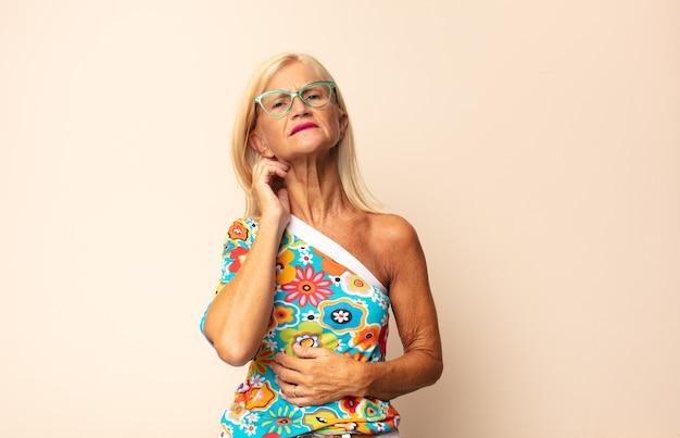 Donna di mezza età che si sente stressata, frustrata e stanca, strofinando il collo dolorante, con uno sguardo preoccupato e turbato Foto Premium