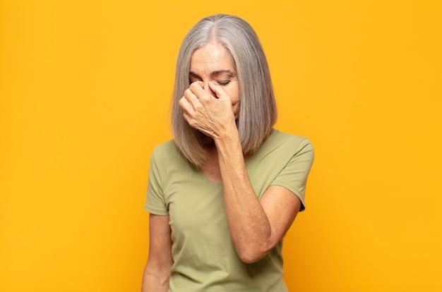Donna di mezza età che si sente stressata, infelice e frustrata, si tocca la fronte e soffre di emicrania o forte mal di testa Foto Premium