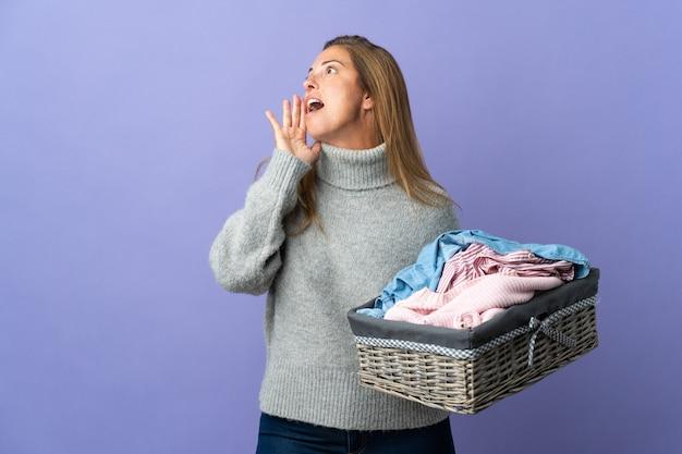 Donna di mezza età che tiene un cesto di vestiti isolato su viola che grida con la bocca spalancata di lato Foto Premium